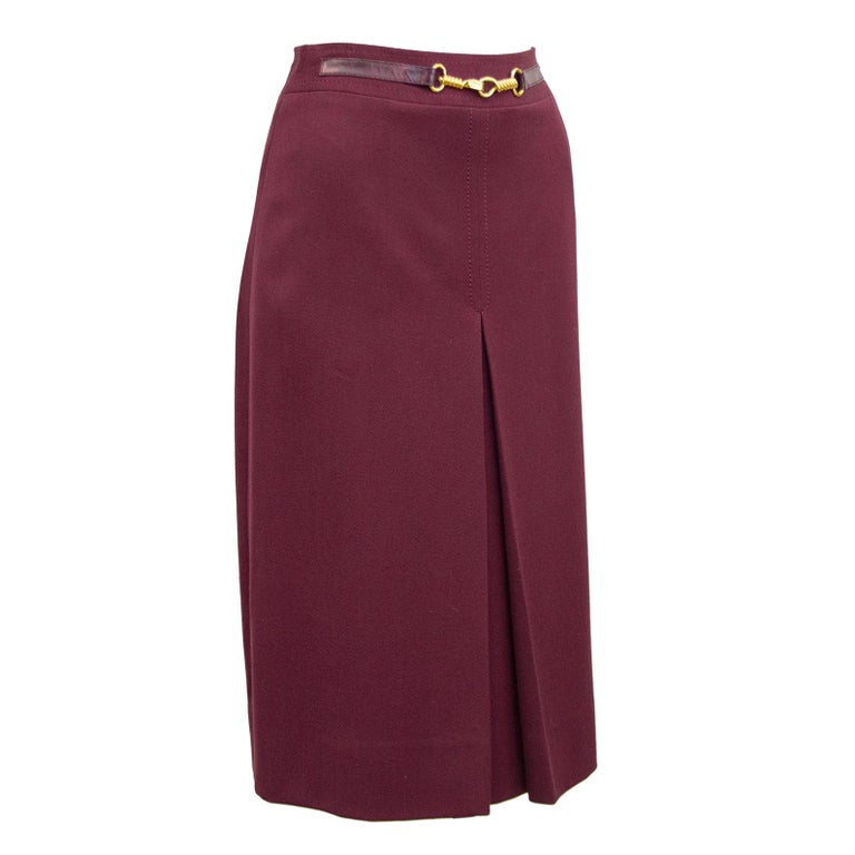 1970's classic Celine maroon wool gabardine skirt with half maroon leather and gold belt at waistband. Inverted stitched single box pleat on the front and back. Overall A line shape. In excellent condition, side zipper with hook and eye. Fits like a