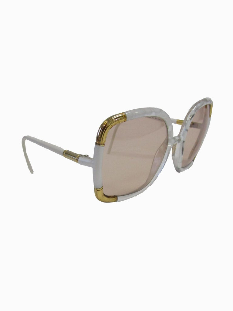 Classic Ted Lapidus Paris sunglasses done in white marbled acrylic with gold hardware. Grey lenses are oversized.  Lens Width-57mm Bridge Width- 15mm Temple (arm) Length - 5in