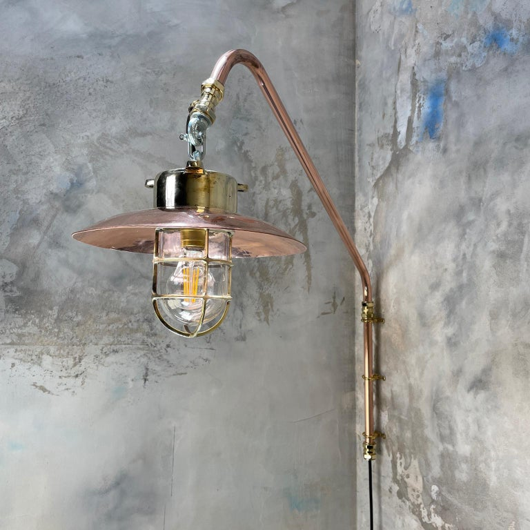 Copper and brass cantilever lamp with brass explosion proof pendant.  A solid cast brass reclaimed light fitting with new copper pipe cantilever, made in house.  The reclaimed explosion proof light was originally used on super tankers and cargo