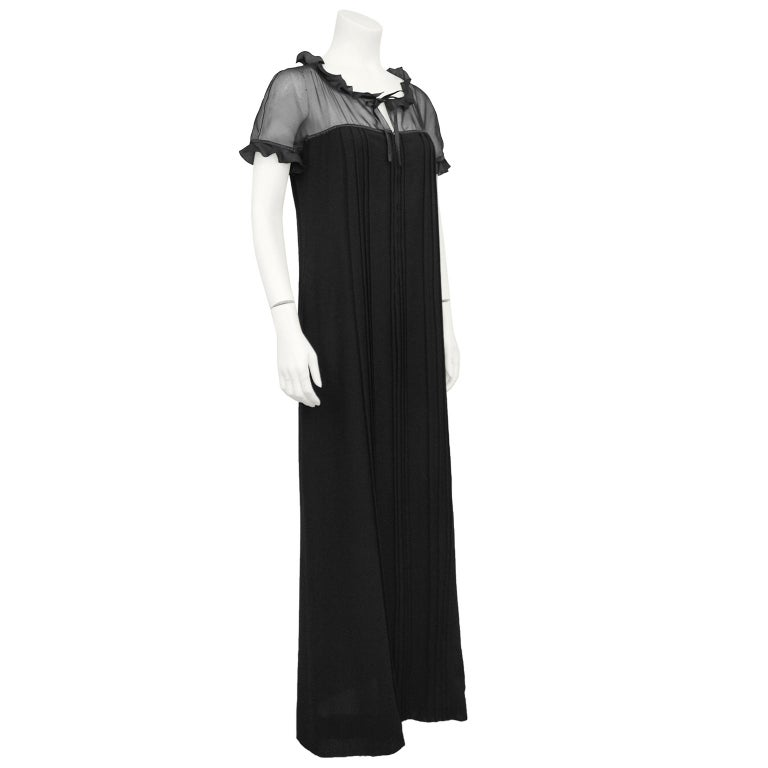 Beautiful 1970s gown by Courreges. Sheer black chiffon yoke and cap sleeves with a black satin ruffle across neckline and hem of sleeves. Tie at neckline creating a small keyhole. The gown then cascades to the floor in black wool with micro stitch