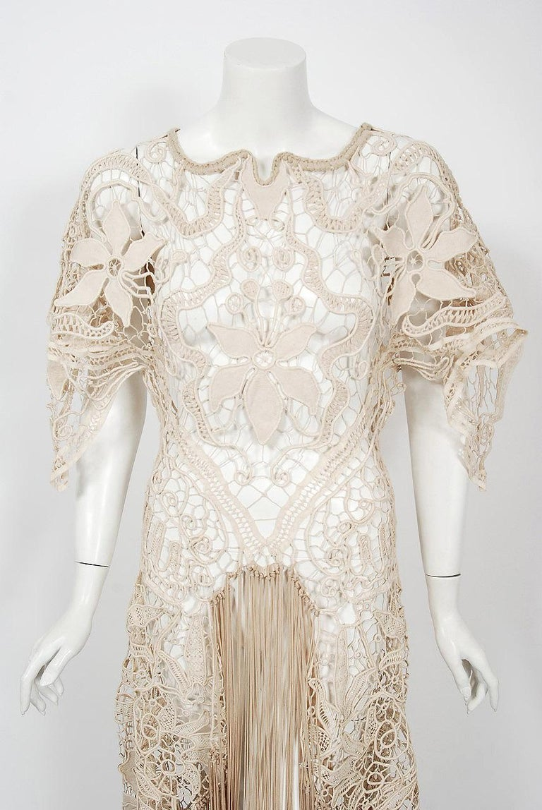An ethereal 1970's British custom couture sheer lace gown that effortlessly mixes the bohemian vibe with 1930's Old Hollywood glamour. The fabric used is breathtaking; hand finished floral motif corded beige tape lace which molds to the body with