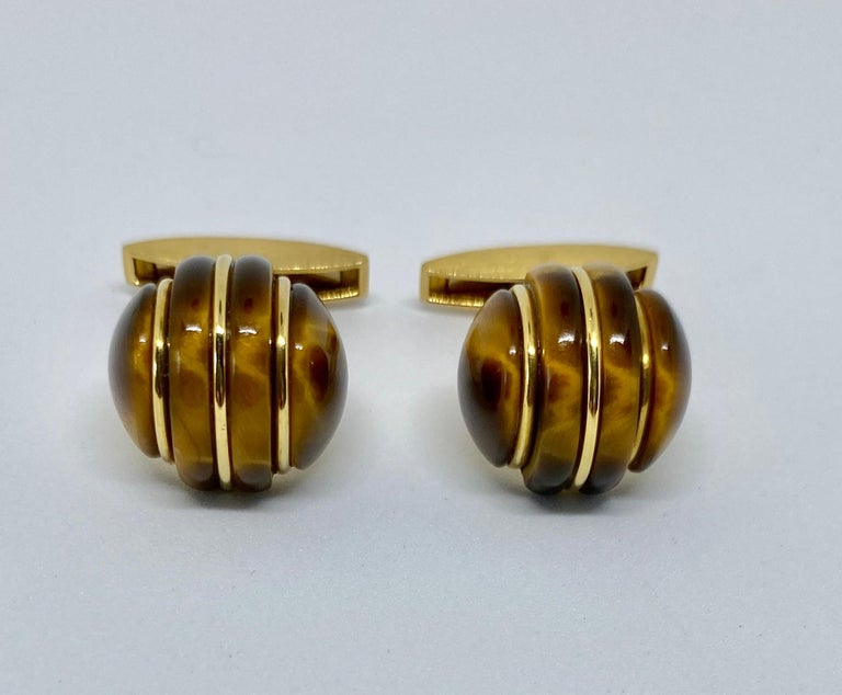 Spectacular, 1970s-era cufflinks made in Germany and featuring two large, carved tiger's eye domes set in 18K yellow gold. The color and quality of the tiger's eye is exceptional, as is the workmanship.  The cufflinks are signed GERMANY and 750