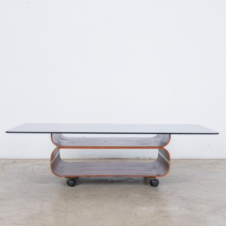A wooden coffee table with glass top on wheels from Denmark, circa 1970. With its bold, curving lines and combination of glass on top rich, dark wood, this table is classic Scandinavian modern. Chic, sleek and practical, this table is waiting to