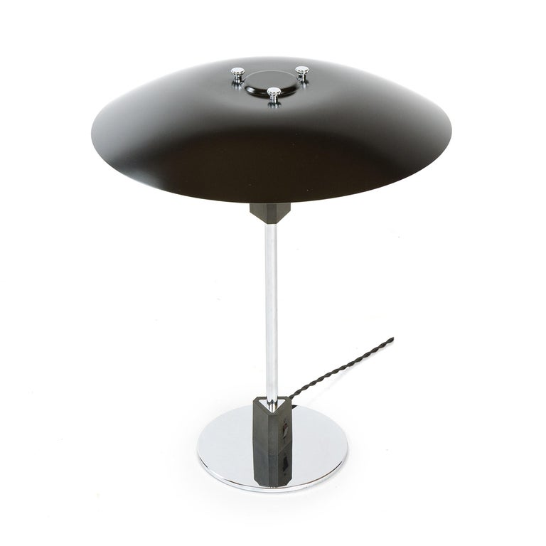 A sculptural desk lamp by Poul Henningsen having a polished chrome stem supporting a concentric three-tiered lacquered aluminum shade, rising from a chromed disc base.