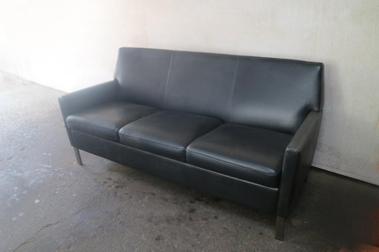 A late 1970s three-seat sofa with original black leather upholstery and brushed steel legs.