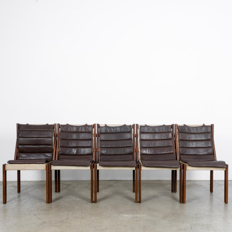 This set of five wooden dining chairs was made in Denmark, circa 1970, and offer comfort and style to your home. The deep brown, padded leather seats are secured to the backs with straps creating a subtle contrast with the clean lines of these