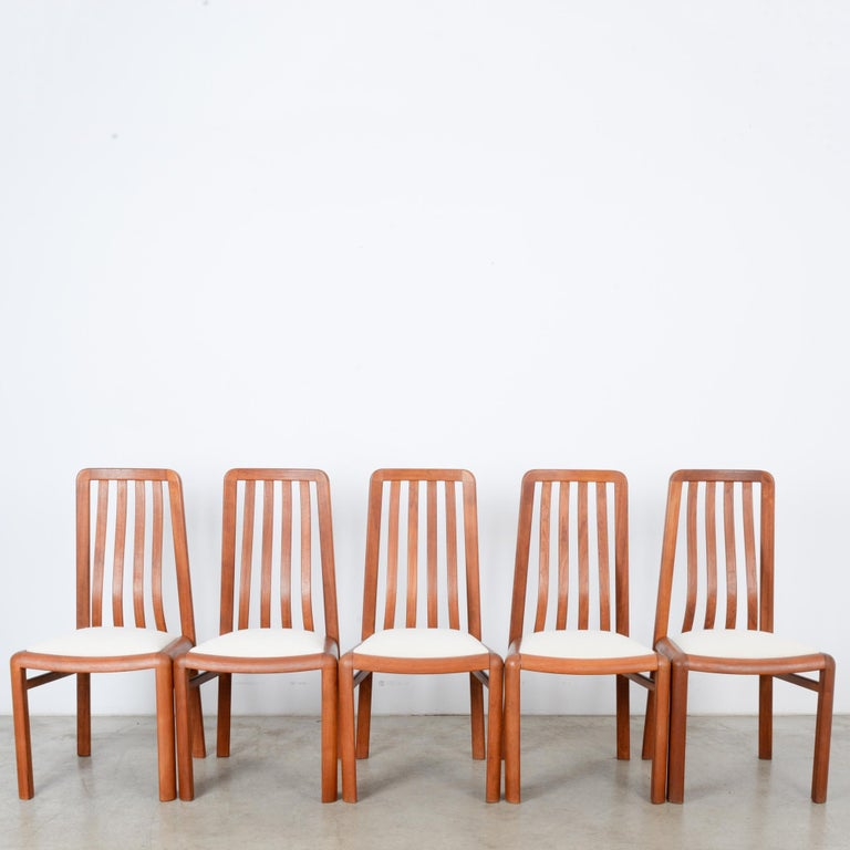 A set of five wooden dining chairs from Denmark, circa 1970. A frame of rosy, softly polished wood with an upholstered white seat. The square profile finds a rhythmic contrast in the fluid curves of the backrest. Softly curved corners and the simple