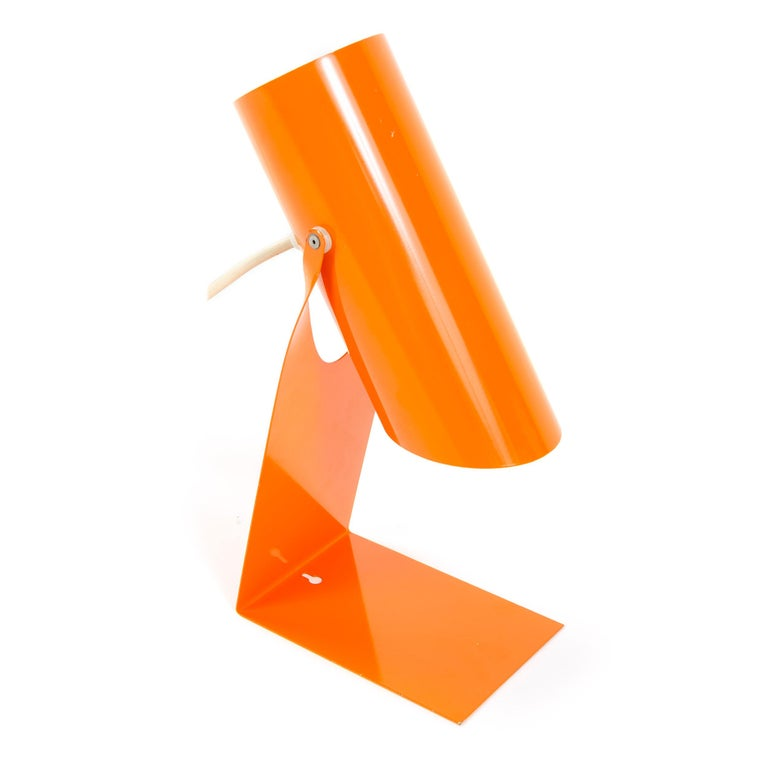 A versatile and vibrant orange enamel lighting device that primarily functions in a desk or table capacity but has a keyhole slot which allows it to function additionally as a wall lamp. The base is one piece of flat, folded steel cradling a