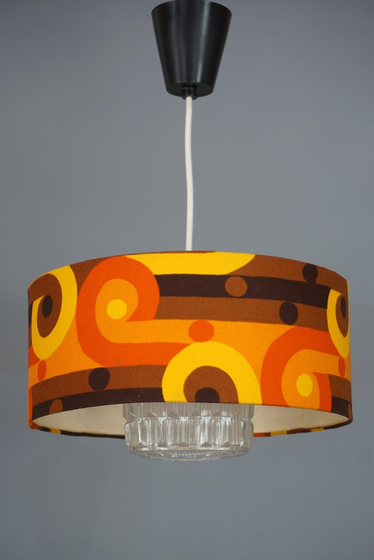 Sculpted glass and psychedelic fabric for this chandelier in total retro and 1970s look.