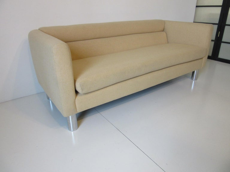 A vintage 1970s sofa or loveseat with fitted back and loose bottom cushion with chromed round tube shaped metal legs and original wool blended fabric, retains the manufactures label and ticking by David Edward Furniture Ltd. A very modern
