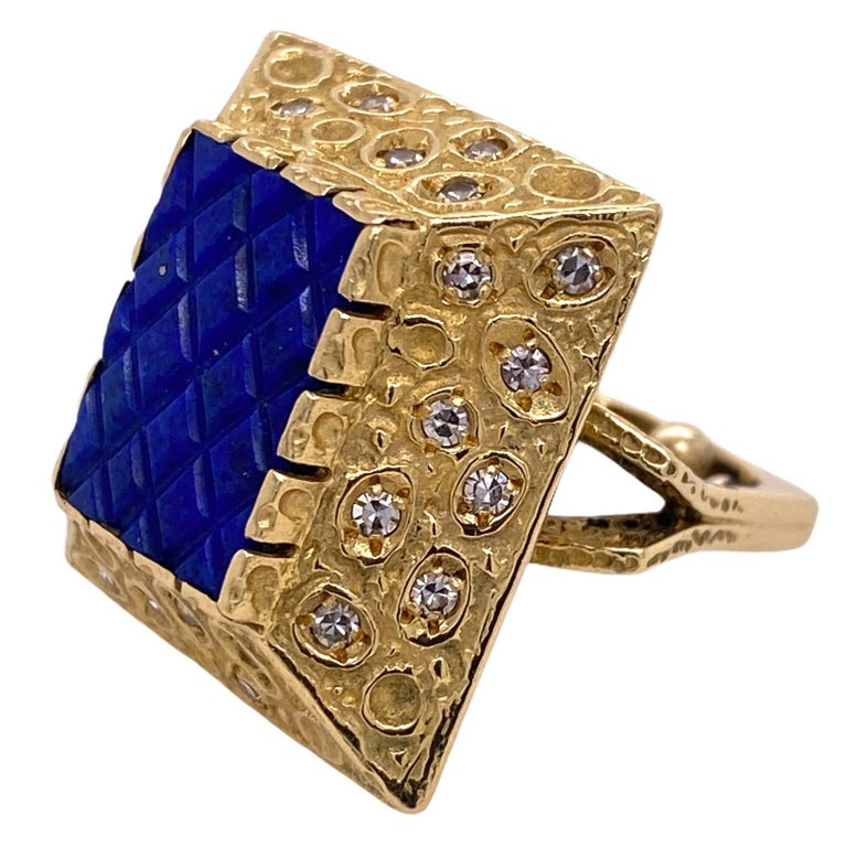 Fabulous lapis lazuli and diamond cocktail ring fashioned in 14 karat yellow gold. The ring features a carved lapis top with 27 surrounding diamonds weighing .50 CTW. The ring is currently size 5 (with sizing beads), size 6 removed. This ring can be