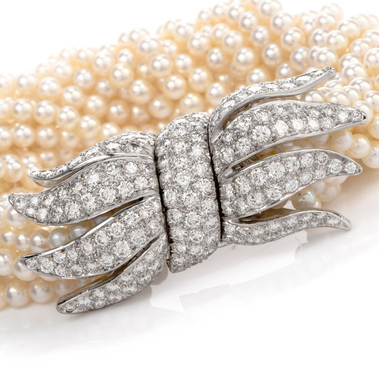 This Vintage Diamond and Multistrand Pearl Bracelet is inspired with an extraordinary Peacock style capping on the ends and crafted in Platinum. This bracelet is sure to Light the room as it's worn yet offers a subtle accent to complete any
