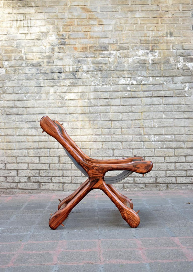 This is a Sloucher chair from 1970s. It's a piece with amazing woodcraft. Very beautiful solid tropical wood. Impeccable black leather seat. Very comfortable and unique design.
