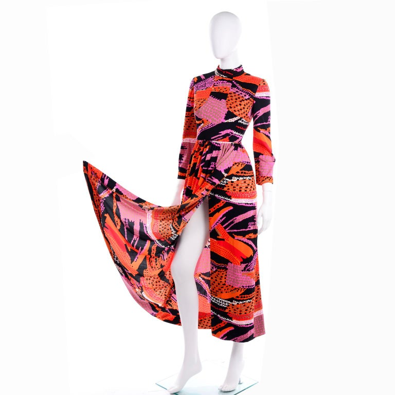 This great vintage early 1970's Dynasty knit dress is in an incredible orange, purple, black and pink, abstract print. The bust is lined and the dress closes with a hook and eye on the back of the neckline as well as a metal zipper down the center