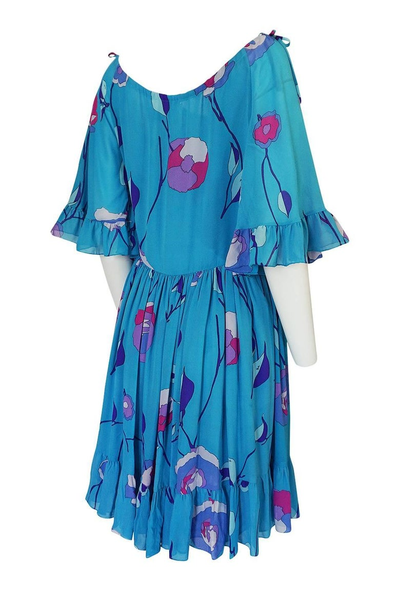 The color of this Pucci dress is wonderful. It is a beautiful shade of turquoise blue and the pops of pink and purple work perfectly against that backdrop. The cut is very flattering and forgiving and has a very romantic feel to it. This is not your