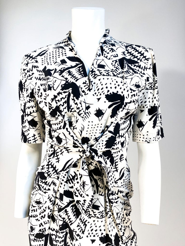 Late 1970s to early 1980s black and white Emmanuelle Khanh silk dress featuring an abstract print. The sleeves are elbow length with minor bathing on top of the shoulder and the was it has center panels that have a a sailor type tie for a proper