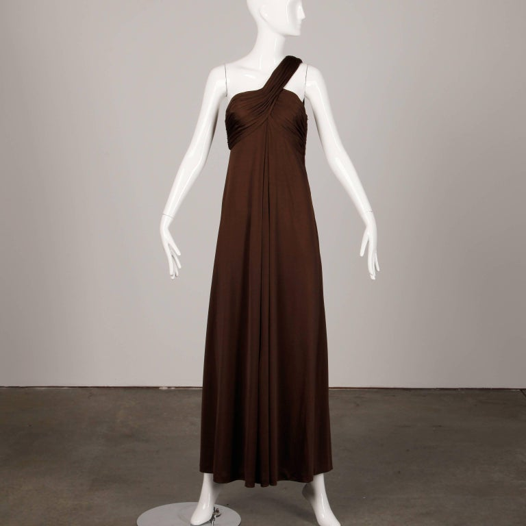 Gorgeous vintage brown jersey knit one-shoulder dress by Estevez. Fully lined, with side zip and hook closure and shoulder hook closure. Light weight slinky high quality jersey knit 100% polyester. The marked size is 6, but the dress fits like a