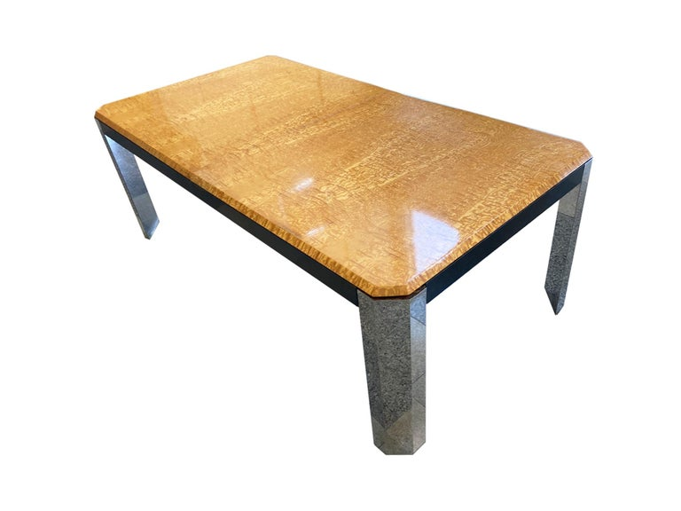 1970s extendable dining table in the style of Milo Baughman. This table combines Mid-Century Modern simplicity with the embellishment of materials like burlwood and chrome. The tabletop is patterned with a honey-yellow burl, while the legs are