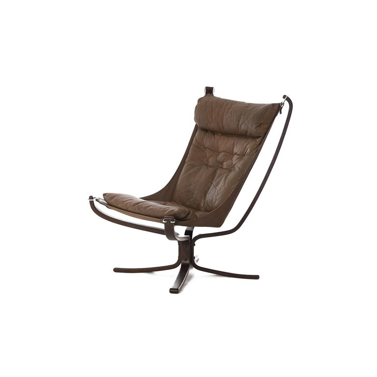Iconic X-framed falcon lounge chair designed by Sigurd Ressell for Vatne Møbler, Norway circa 1970. Featuring a sculptural bentwood beech wood frame, brown canvas sling and dark olive-brown leather cushion. The hammock style floating seat creates a