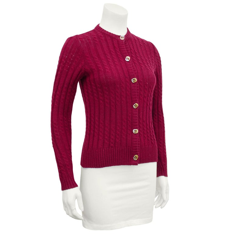 Chic 1970's burgundy wool ribbed and cable knit fitted cardigan with silver and gold plated Ferragamo logo buttons down the front. In excellent condition, no signs of wear. Fits like a US size 0-4 depending on how you like your fit.