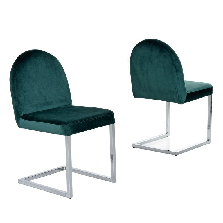 Exquisite chrome cantilever Baughman style dining chairs. The chairs were reupholstered with a luxurious forest green velvet that feels just as smooth as butter. The arched backs provide balance to all the modernist 90 degree angles on the chrome