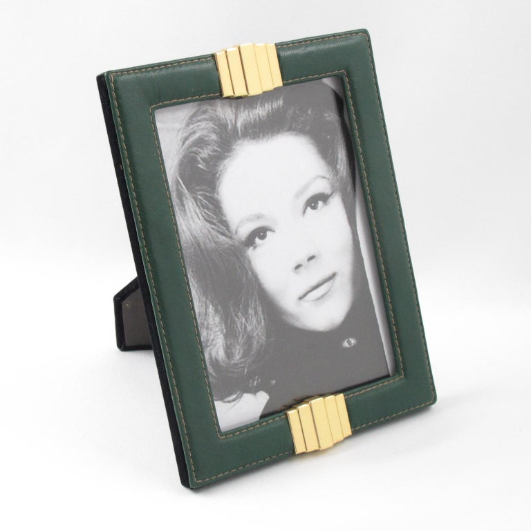 Elegant 1970s French picture photo frame. Forest green leather with pattern and hand-stitched detailing compliment with gilded brass ornament. Easel and back in black velvet and glass protection. Frame can be placed in portrait or in landscape