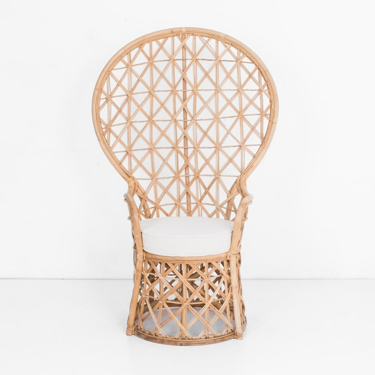 "In typical mid-20th century rattan fashion, an ""Emmanuelle"" style armchair from circa 1950. This throne like chair has a great shape, with a thickly braided intriguing and supportive woven rattan back. Topped with a re-upholstered cotton-linen"