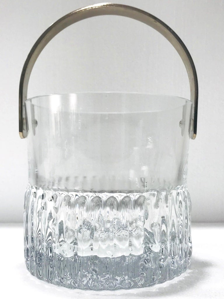 Mid-Century Modern crystal ice bucket with polished edges and stainless steel handle. Features heavyweight handcrafted crystal with fluted edges along resembling icicles or ice cubes, and with ripples on the bottom base. Makes a chic addition to any
