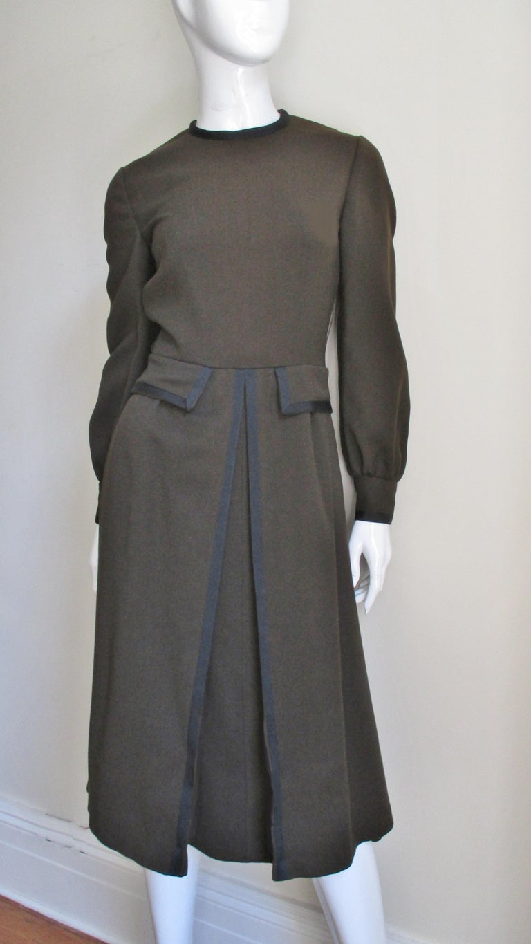 A brown wool dress with black trim from Geoffrey Beene. It has a crew neckline and long slightly full sleeves with black button cuffs. The bodice is fitted with pocket flaps at the waist and functional pockets in the skirt side seams.  The skirt is