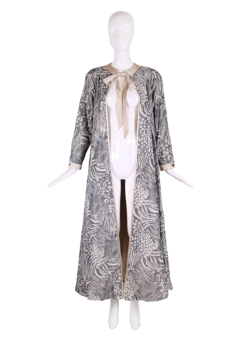 1970's Geoffrey Beene silk taffeta dress coat in grey & cream abstract geometric print with cream silk charmeuse trim, neck ties, and lining. There is a creme silk charmeuse