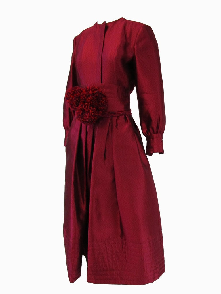 Remarkably designed dress from Geoffrey Beene! This dress features an iridescent silk that truly catches the eye! It opens at the front with hidden zipper closure and also slightly ballooned sleeves that are finished with long cuffs. The dress has