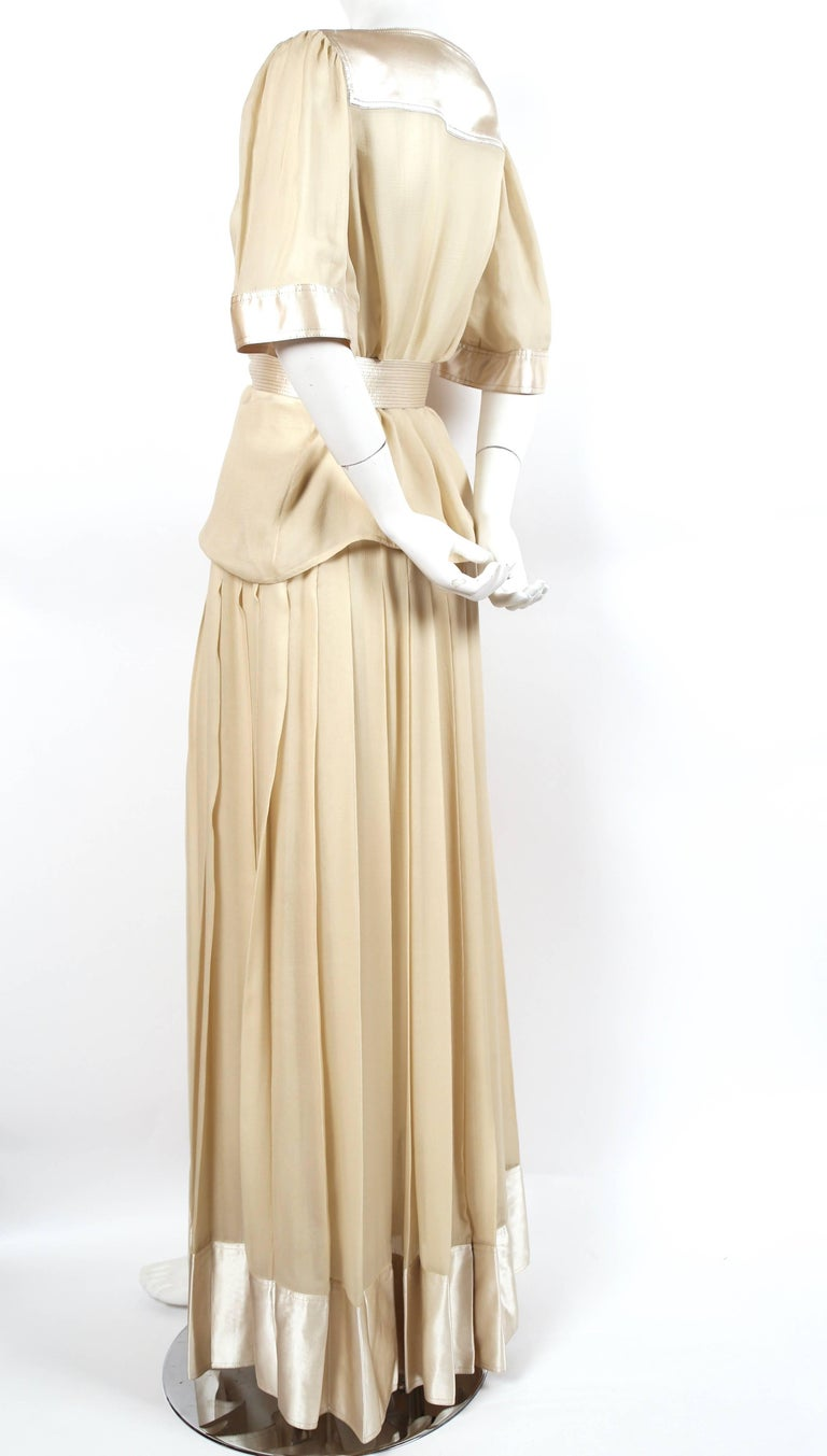 Cream sheer silk ensemble with stain trim and matching belt accented with metallic gold thread designed by Geoffrey Beene dating to the late 1970's. Fits a US 4-6. Top measures approximately 40