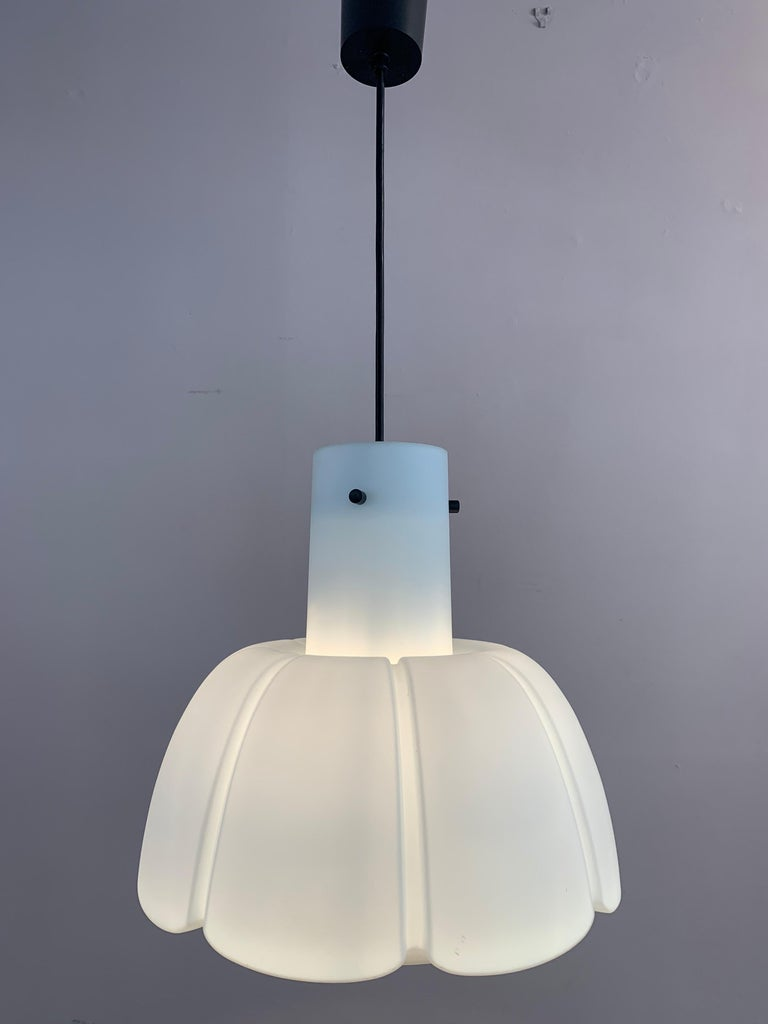 1970s German Peill & Putzler opaline pendant ceiling light formed in the shape of an eight leaf flower. Three black feature screws suspend the shade from the bulb socket holder and height adjustable ceiling wire with matching cup. In very good