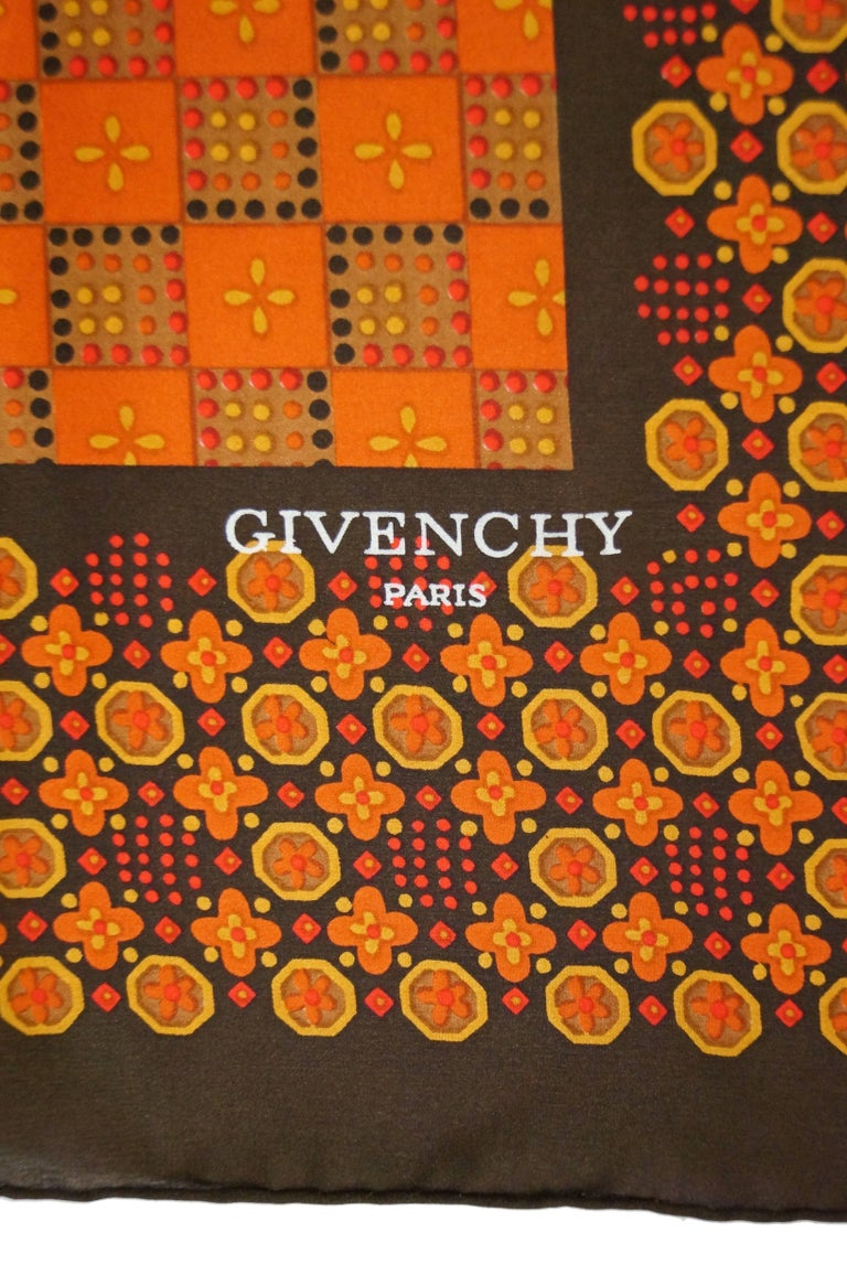 Beautiful large square silk scarf by Givenchy. The scarf has a mostly orange center with a wide brown - orange border. The scarf features geometric patterns incorporating floral elements.