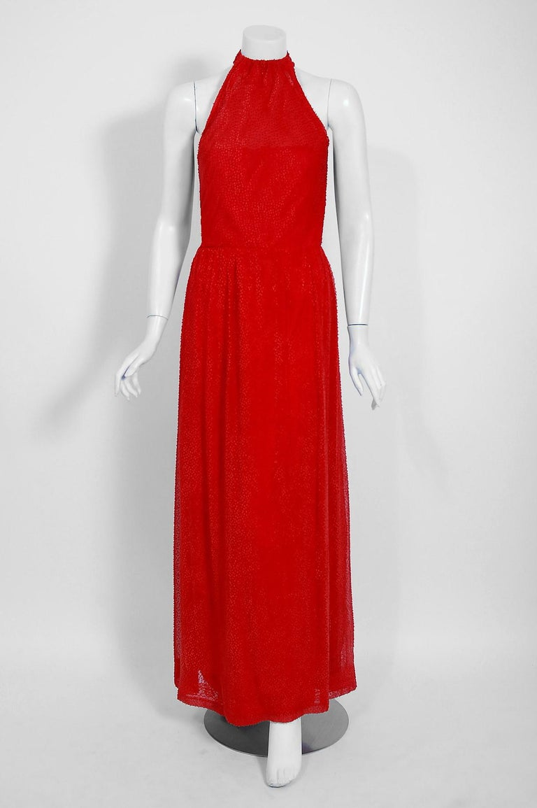 Givenchy, the name itself evokes glamour, refined elegance, simplicity and style. Givenchy's trademark of flowing lines and luxurious fabrics make his work easily recognizable. This gorgeous ruby-red goddess gown, dating back to the mid 1970's, is a