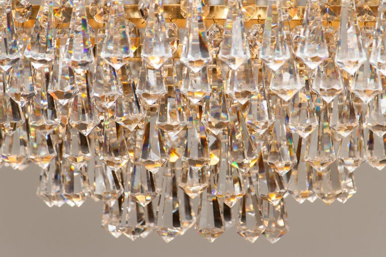 Beautiful gold-plated chandelier attributed to Rejmyre Armaturfabrik Rejmyre, Sweden, 1970s. The chandelier is build up out of six rings and two crowns filled with faceted crystal, total diameter of the fixture is 44cm or 17