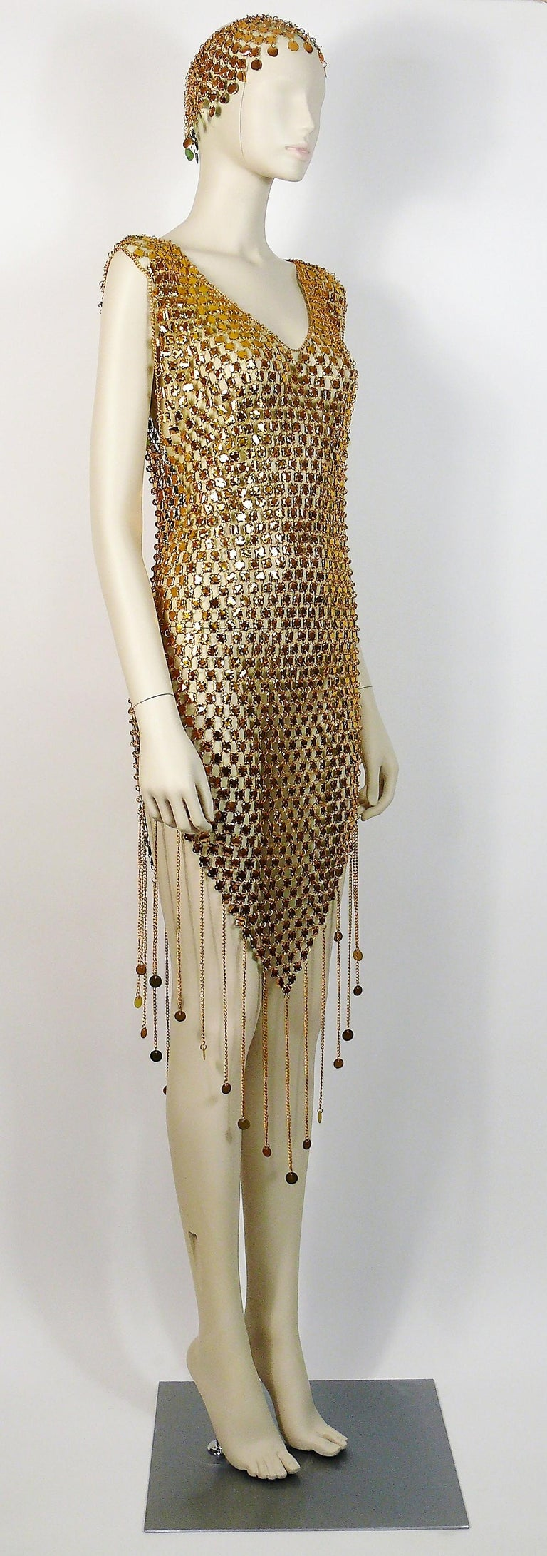 Gorgeous vintage 1970s chainmail dress featuring gold toned rhodoid quadrilobe discs linked with aluminium rings and fringes.  Slips on to wear.  The dress comes with its matching hat.  Photographied on a XS size mannequin.  Indicative measurements