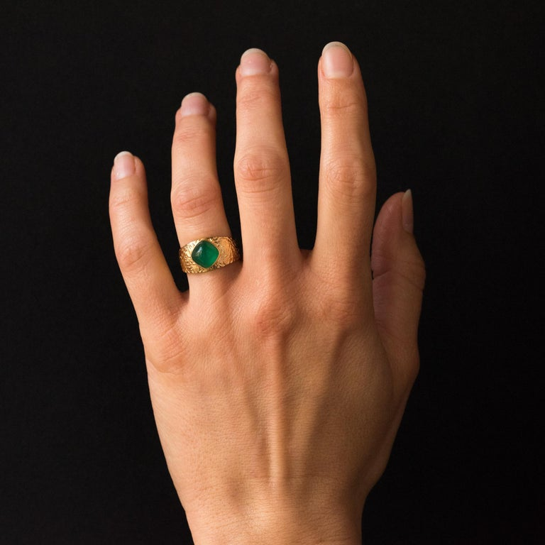 Ring in 18 karat yellow gold. This retro ring is adorned on the top with a green cabochon agate in a closed setting, surrounded by a carving on the top of the ring. Agate total weight: about 1.85 carat. Height: 10.2 mm, width: 9.5 mm, thickness: