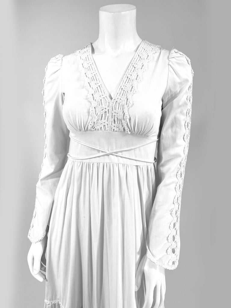 1970s soft cream colored cotton Gunne Sax Full length granny style dress with machine crochet trim along the full sleeves, deep v-neckline, and wide skirt ruffles. At the was it there is a criss-cross tie.