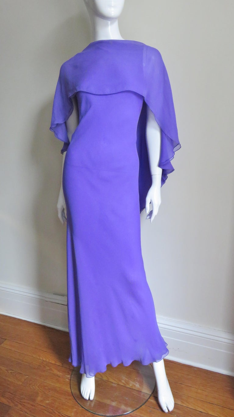 A gorgeous purple silk dress by Halston. It is a sleeveless semi fitted long sheath with a panel across the front chest and shoulders angling and widening towards the center back framing a deep V then continuing to the hem creating cape effect.  The