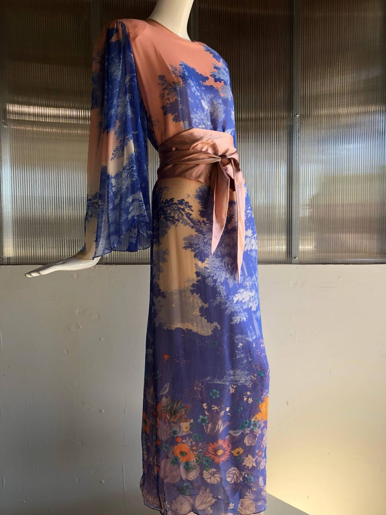 This beautiful 1970s Hanae Mori silk chiffon maxi dress is printed with a stunning meadow tableau of trees and wildflowers, in coral and blues.  Matching sash belt included.  Sleeves are loose, flowing and sheer.  High side slit. Dress is lined.