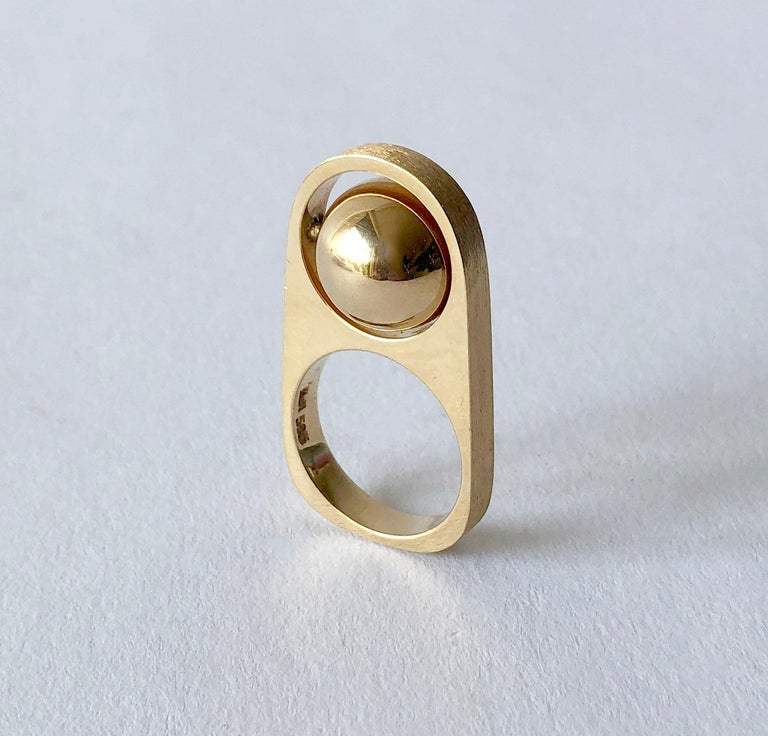 1970's 14k gold spinning ball ring created by Han Hansen of Denmark.  Ring has a Florentine finish on its small sides, while the rest of the ring has a polished finish.  It is a finger size 5.75 - 6 and stands .75