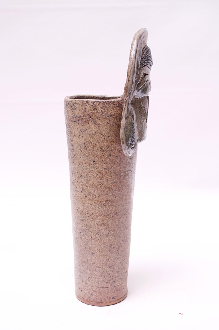 Striking and unique stoneware vase made in 1976 by ceramicist, Pollack. Interesting incorporation of textures and patterns - a matte-beige mottled surface with a slight metallic sheen and applied metallic fragments. Signed