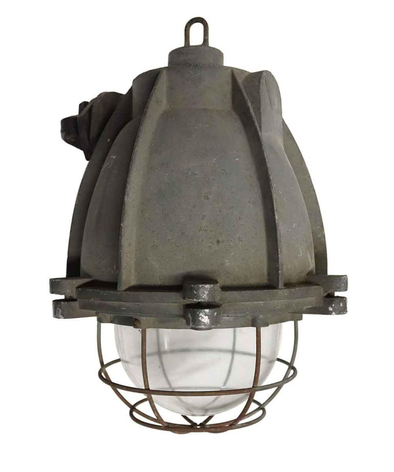 1970s vintage heavy cast aluminum light with cage covered glass. Industrial style pendant from Europe. Single socket. This can be seen at our 400 Gilligan St location in Scranton, PA.