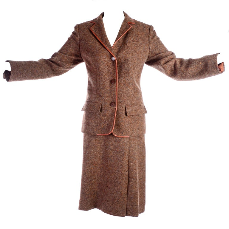 This is a 1970's vintage Hermes 2 piece suit with a skirt and a blazer in a pretty brown and tan wool tweed trimmed in leather.  The blazer closes with leather Hermes monogram buttons. The suit is fully lined, was made in France, and is marked a