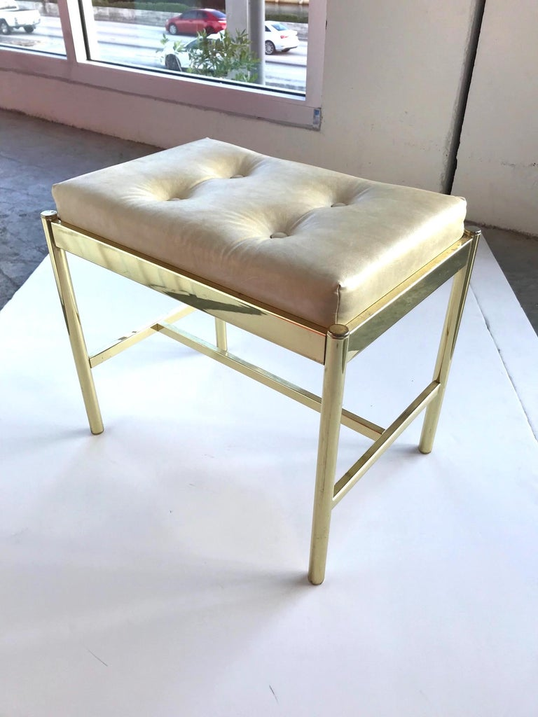Chic Mid-Century Modern vanity bench or vanity stool with brass frame, in easy to clean Naugahyde leather in hues of tan, or beige. Bench has a rectangular form and features streamline crossbar base and button details on the seat.