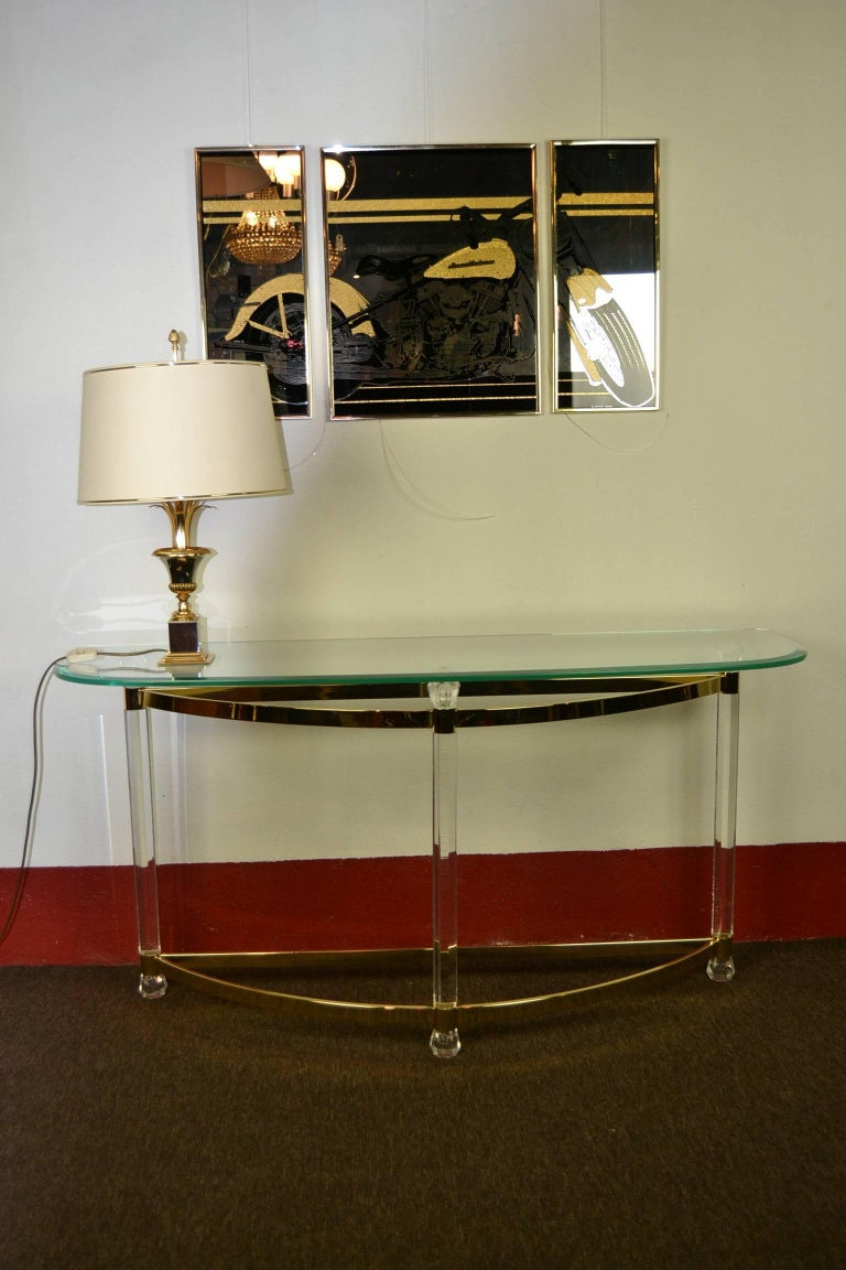 Elegant 1970s Lucite Console Table or Side Table with Glass Top.   This Table in Hollywood Regency Style  is made of Clear Perspex -  Plexiglass with Brass Feet ,  and has a Rounded Facet Glass Top.  This Stylish Table is in good vintage condition.