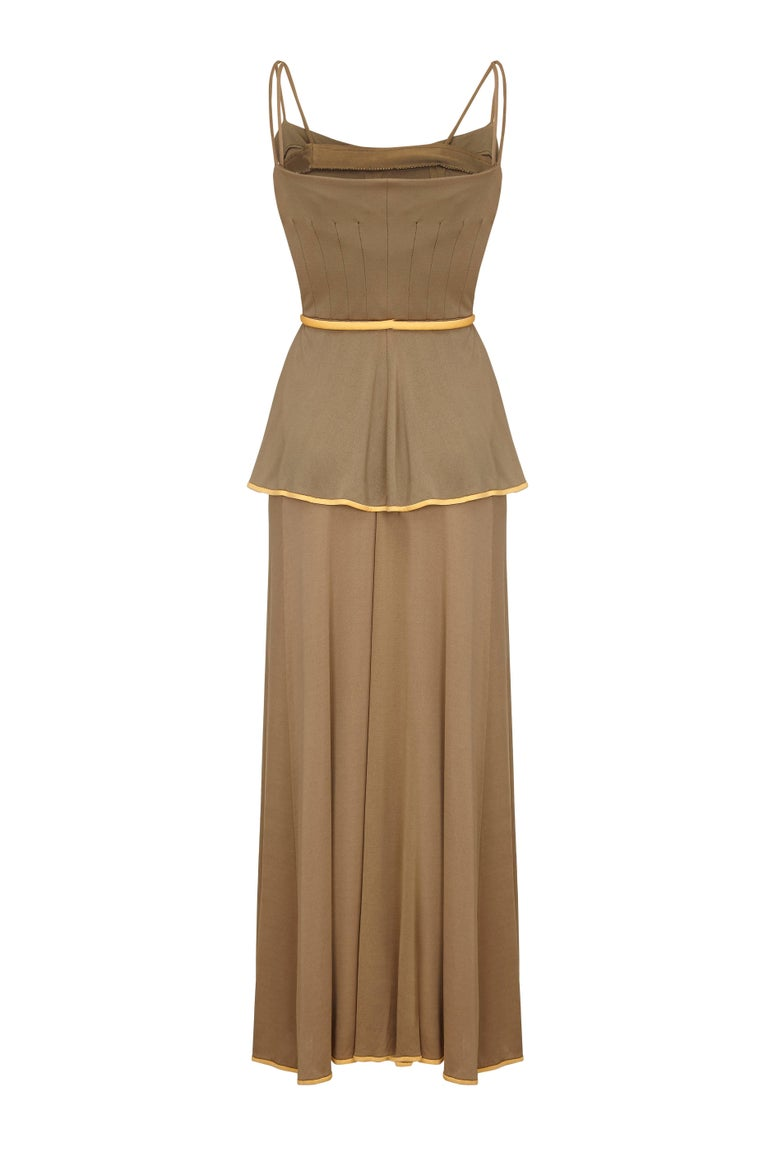 This charming  1970s olive toned silk jersey peasant style 2 piece is by American label Horiko for Saks 5th Avenue.  It is comprised of a floor length maxi skirt and strappy peasant vest with a pretty peplum waist.   Both pieces feature piped seams