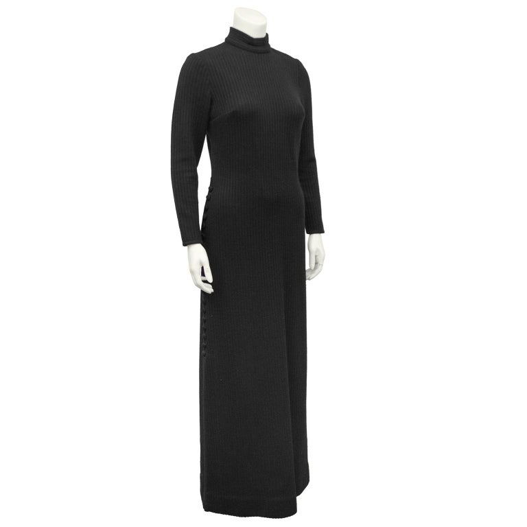 Stunning 1970's black ribbed body-con knit gown from Italian designer Lucia Knitting Mills. Mock neck, long sleeves with covered buttons down the left leg. Darts at bust. 19