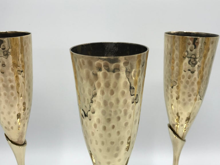 Listed is a fabulous, set of four, 1970s Italian brass champagne flutes with a hammered look. Heavy, weighing nearly 3lbs for the set of four.
